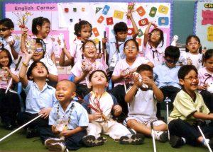 Jogos didáticos para crianças com deficiência visual. A imagem mostra várias crianças com deficiência visual em sala de aula realizando jogos educativos