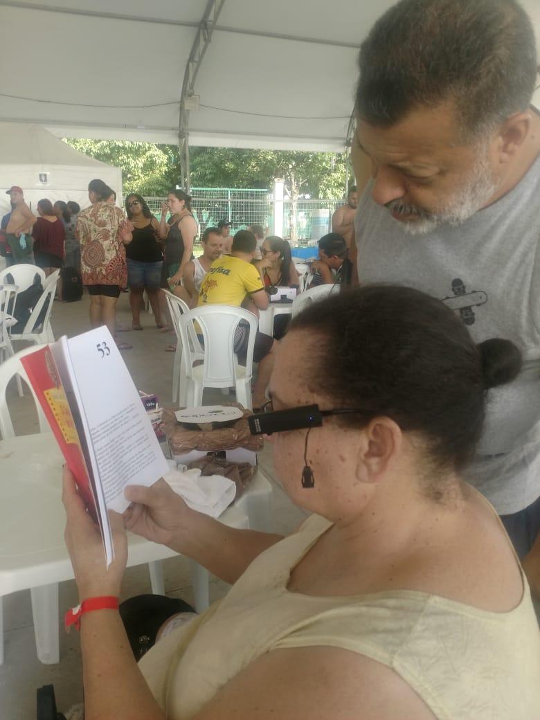 #PraCegoVer #PraTodosVerem Foto de uma mulher lendo um livro com o OrCam MyEye, ao seu lado um homem que está interessado na leitura.