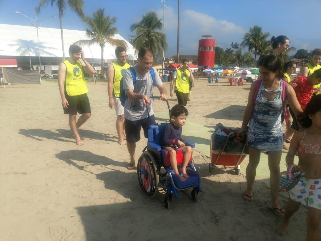 #PraCegoVer #PraTodosVerem Foto de uma criança, com deficiência física, sendo levado por um acompanhante pela praia, ao seu redor pessoas que fazem parte do projeto.