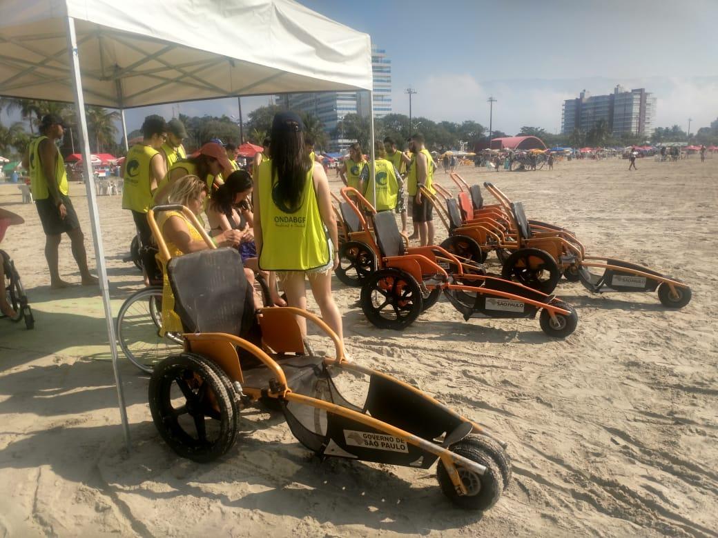 #PraCegoVer #PraTodosVerem Foto da barraca em que estavam as cadeiras de rodas adaptadas para o mar.  Na foto podemos ver integrantes do projeto.