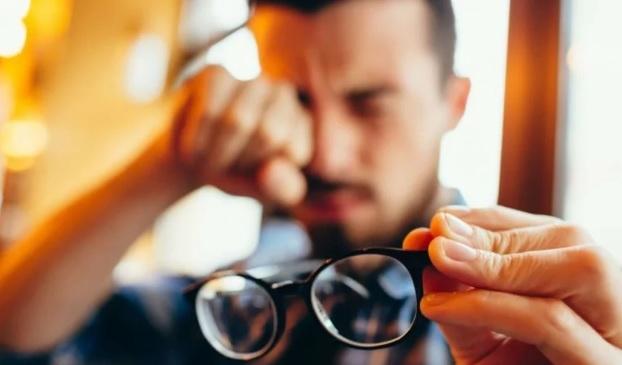 imagem embaçada que mostra um rapaz jovem segurando seus óculos com a mão esquerda e com mão direita ele coça seu olho direito